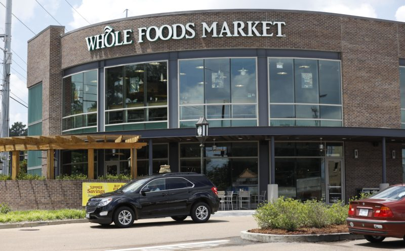 AP PHOTO Customers drive past this Whole Foods Market store in Jackson, Miss., Friday. Amazon is buying Whole Foods Market in a deal valued at $13.7 billion, uniting the on-line giant with the grocery store chain that touts fresh organic foods.