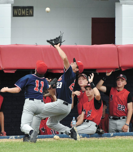 T-R PHOTO BY ANNE VANCE • Marshalltown pitcher Tate Kuehner (11) gives chase as third baseman Sam Irwin (23) makes a sliding catch at the base of North Polk's dugout during the fourth inning of Friday's non-conference baseball game at MHS. North Polk shut out the Bobcats, 2-0, for its first win in the series since 2013.