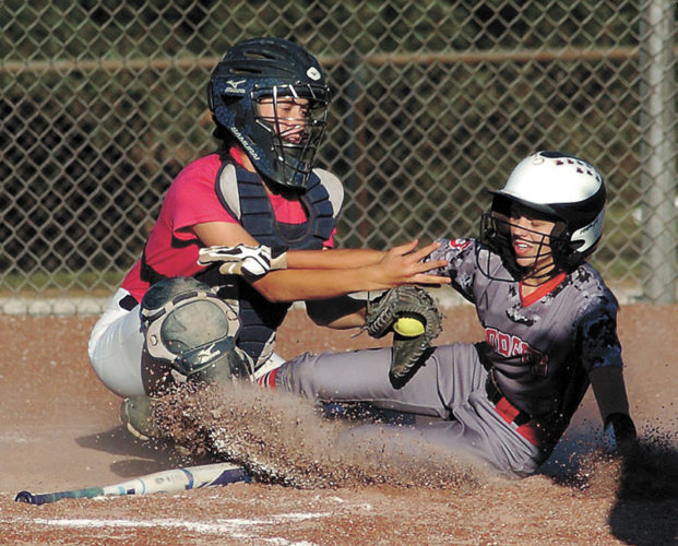 T-R PHOTO BY ROSS THEDE • Marshalltown catcher Erica Johnson, left, makes the tag on a Fort Dodge baserunner during the fifth inning of the opening game of Monday's CIML Iowa Conference softball doubleheader against the Dodgers. Fort Dodge swept the conference twinbill, winning 15-8 and 10-4.