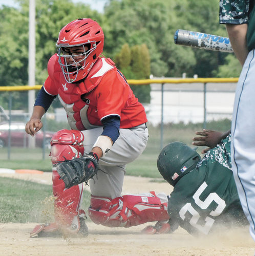 T-R PHOTO BY ANNE VANCE • Marshalltown catcher Miguel Torrez, left, attempts to tag out a Des Moines North baserunner during Thursday's CIML doubleheader in Des Moines. The Bobcats swept North, 13-3 and 16-2, both games ending after five innings.