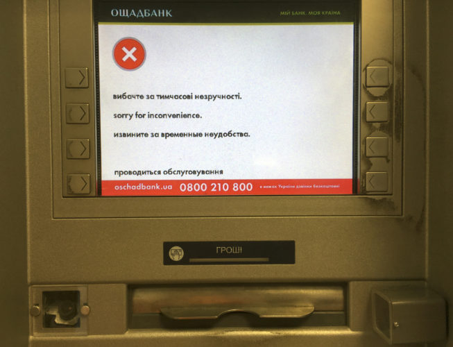 "AP PHOTO A screen of an idle virus affected cash machine in a state-run OshchadBank says ""Sorry for inconvenience/Under repair"" in Kiev, Ukraine, Wednesday."