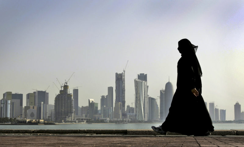 AP PHOTO In this May 14, 2010 file photo, a Qatari woman walks in front of the city skyline in Doha, Qatar. Qatar likely faces a deadline this weekend to comply with a list of demands issued to it by Arab nations that have cut diplomatic ties to the energy-rich country, though its leaders already have dismissed the ultimatum.