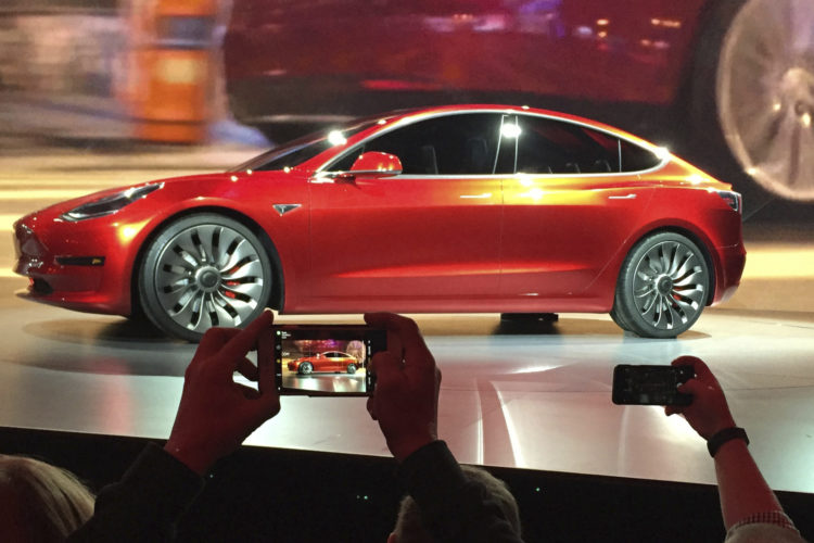 In this March 31, 2016, file photo, Tesla Motors unveils the new lower-priced Model 3 sedan at the Tesla Motors design studio in Hawthorne, Calif. Electric car maker Tesla said on Monday, July 3, 2017, that its Model 3 car will go on sale on Friday. (AP Photo/Justin Pritchard, File)