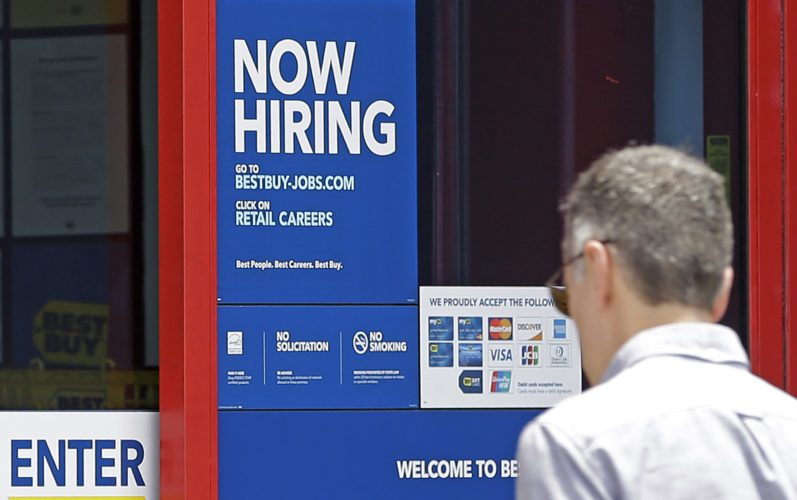 """AP PHOTO In this May 22, photo, a """"Now Hiring"""" sign welcomes a customer entering a Best Buy store in Hialeah, Fla. U.S. employers added a robust 222,000 jobs in June, the most in four months, a reassuring sign that businesses may be confident enough to keep hiring despite a slow-growing economy."""