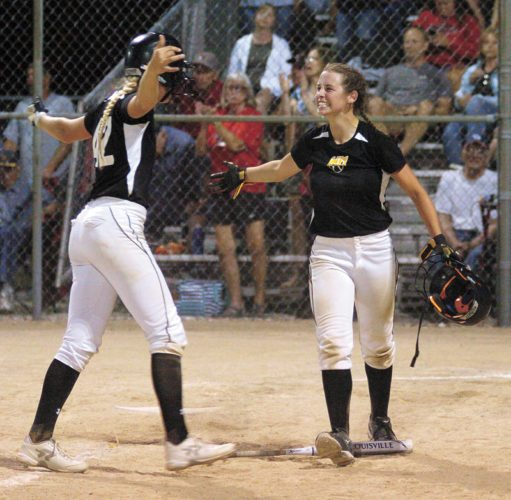 T-R PHOTO BY ROSS THEDE • West Marshall's Georgia Porter, right, goes to hug teammate Brooke Snider after Snider's ground ball to first base drove in Porter as the game-winning run in the bottom of the ninth inning of Friday's Class 3A Region 8 semifinal in State Center. The Trojans won 5-4.