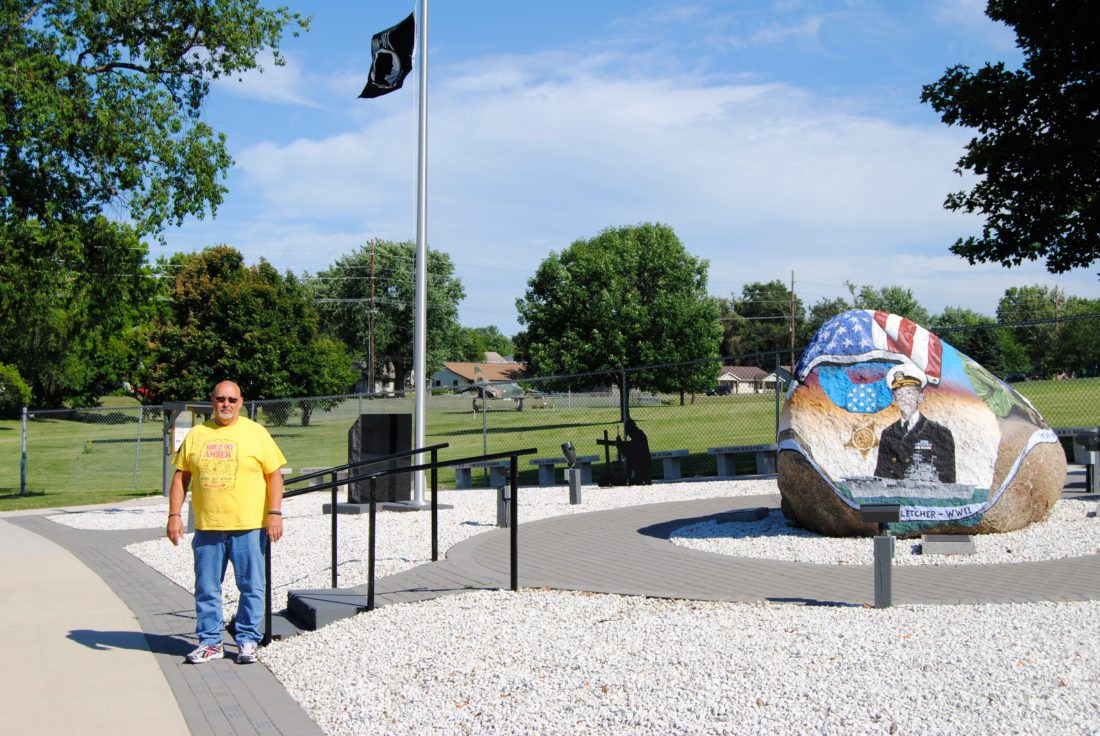 T-R PHOTO BY JEFF HUTTON American Legion Post 46 Vice Commander Kevin Huseboe stands next to the Freedom Rock, located on the American Legion grounds. Huseboe and members of the American Legion Riders Post 46 group want to construct a memorial pathway from the Freedom Rock to the back entrance of the F4 Phantom fighter jet, in the background, that sits parallel to South 6th Street.