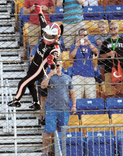 T-R PHOTO BY MARK GEORGE • Helio Castroneves climbs the fence as he celebrates with fans after winning the IndyCar Series Iowa Corn Indy 300 on Sunday at Iowa Speedway in Newton.