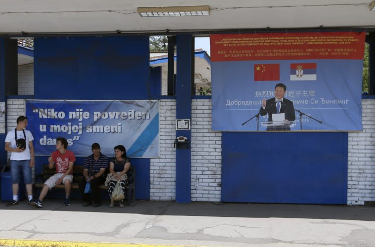 """AP PHOTO In this photo taken June 29, workers rest near billboard showing Chinese President Xi Jinping, reading: """"Welcome President"""", right, and billboard reading: """"Nobody was hurt in my shift today"""" in front of the Zelezara Smederevo steel mill, in the city of Smederevo, 45 kilometers east of Belgrade, Serbia. When U.S. Steel sold its loss-making smelter in Serbia to the government for $1 in 2012, few thought the communist-era factory would ever be revived."""