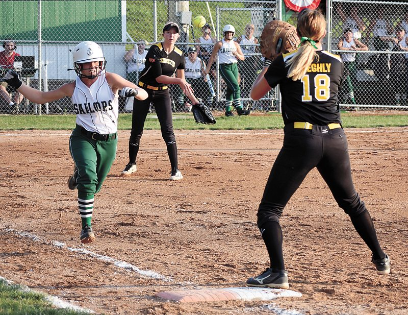 T-R PHOTO BY THORN COMPTON • BCLUW pitcher Samantha Ubben (16) fires the ball to first baseman Jordyn Beeghly (18) while Waterloo Columbus freshman Emily Mollenhoff legs it out during the Comets 1-0 loss in 11 innings to the Sailors on Monday night.