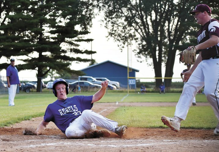 T-R PHOTO BY THORN COMPTON • Gladbrook-Reinbeck junior Kyle Koppen (20) slides into home plate as he scores off a wild pitch from Grundy Center pitcher Braidan Buhrow in the first inning of the Rebels' 11-1 victory over the Spartans.
