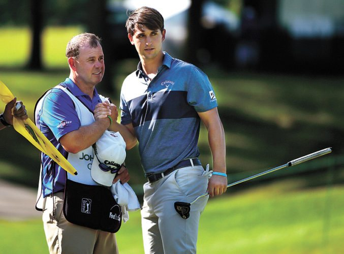 AP PHOTO • Ollie Schniederjans, right, shakes hands with his caddie after sinking a putt on the ninth hole to end his day with a share of the first-round lead at the John Deere Classic on Thursday at TPC Deere Run in Silvis, Ill.