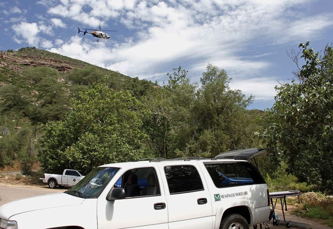 A Department of Public Safety helicopter hovers over as a mortuary vehicle awaits for victims on the parking lot of Water Well Campground in the Tonto National Forest, Ariz, Sunday morning, July 16, 2017, following Saturday's deadly flash-flooding at Cold Springs canyon. The flooding came after a severe thunderstorm pounded down on a nearby remote area that had been burned by a recent wildfire, Water Wheel Fire and Medical District Fire Chief Ron Sattelmaier said. (Alexis Bechman/Payson Roundup via AP)