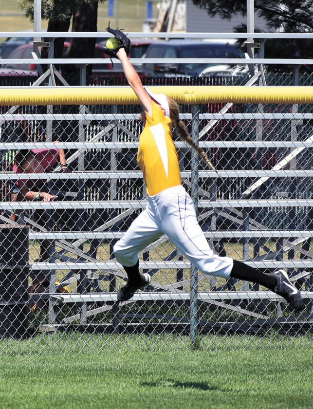 T-R PHOTO BY THORN COMPTON • West Marshall sophomore Kayla Cripps takes to the sky to catch a high fly ball during the Trojans win over Boyden-Hull/Rock Valley in the seventh-place match in the Class 3A bracket of the Iowa Girls' High School State Softball Championships on Wednesday.