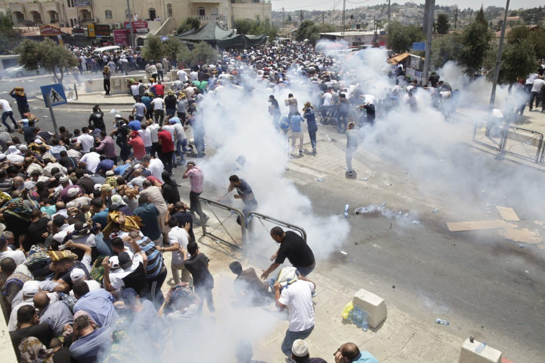 AP PHOTO Palestinians run away from tear gas thrown by Israeli police officers outside Jerusalem's Old City, Friday. Israel police severely restricted Muslim access to a contested shrine in Jerusalem's Old City on Friday to prevent protests over the installation of metal detectors at the holy site.