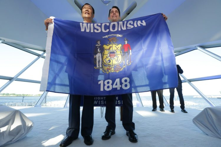 AP PHOTO Foxconn Chairman Terry Gou, left, and Gov. Scott Walker hold the Wisconsin flag to celebrate their $10 billion investment to build a display panel plant in Wisconsin, at the Milwaukee Art Museum in Milwaukee, Wis., Thursday.