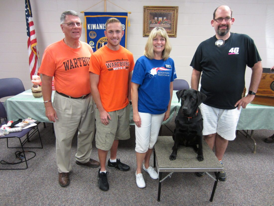 CONTRIBUTED PHOTO Matins Kiwanis members Alan Hilleman and Frank Moran welcome Marit Beisner and her son Luke along with their Black Lab, Victor, as they presented a program on Retrieving Freedom program for the training of therapy and service dogs that is closely working with Wartburg College.