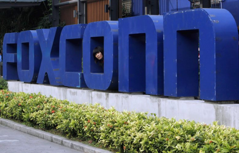 FILE - In this May 27, 2010 file photo, a worker looks out through the logo at the entrance of the Foxconn complex in the southern Chinese city of Shenzhen. Conservationists are lining up to oppose Republican plans to eliminate key environmental regulations as part of an incentive package to lure a $10 billion Foxconn electronics plant to southeastern Wisconsin. Gov. Scott Walker's incentives bill would exempt the company from environmental impact statements and state permits for filling wetlands and building on lake beds. (AP Photo/Kin Cheung, File)