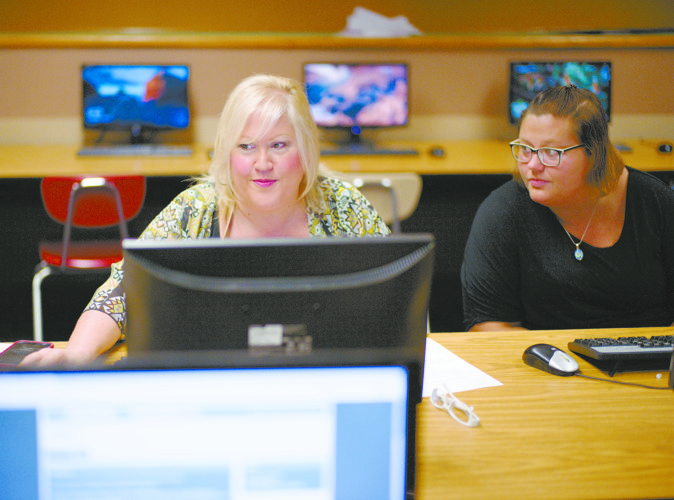 In this Thursday, July 27, 2017, photo, Cheryl Bast, left, is accompanied by her daughter Liz Pierson, as she works on an application for a position with Omaha Public Schools, during a job fair held at Omaha South High School in Omaha, Neb. On Friday, Aug. 4, 2017, the U.S. government issues the July jobs report. (AP Photo/Nati Harnik)