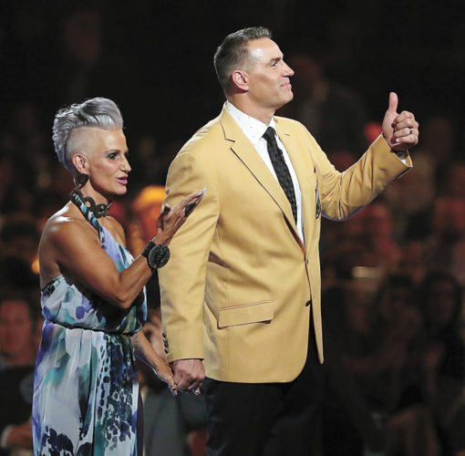 AP PHOTO • Brenda, left, and Kurt Warner wave to the crowd after Kurt received his gold jacket during the Pro Football Hall of Fame Festival Enshrinees' Gold Jacket Dinner on Friday at the Canton Memorial Civic Center in Canton, Ohio.