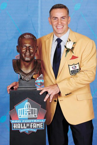 AP PHOTO • Former NFL quarterback Kurt Warner poses with his bust during inductions at the Pro Football Hall of Fame on Saturday in Canton, Ohio.
