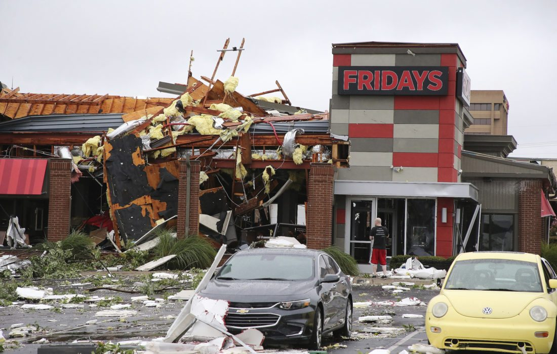 A man stands outside a Fridays restaurant after a storm moved through the area in Tulsa, Okla., Sunday, Aug. 6, 2017. A possible tornado struck near midtown Tulsa and causing power outages and roof damage to businesses. (Tom Gilbert/Tulsa World via AP)