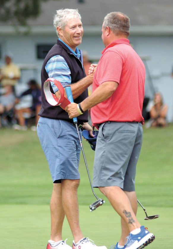 T-R PHOTO BY ROSS THEDE • Bob Brooks, left, is congratulated by Troy Underhill after Brooks tapped in for par on the 18th green to win the 30th annual Times-Repbulican City Golf Tournament championship on Sunday at the American Legion Memorial Golf Course. It's the first City title for Brooks, who shot  67-67—134 for a two-stroke victory. Underhill placed fifth.