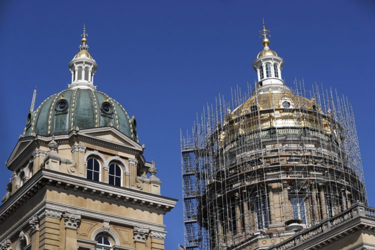 Scaffolding wraps around the dome of the Iowa Capitol building, Wednesday, Aug. 9, 2017, in Des Moines, Iowa. About two dozen workers are spending a hot summer on scaffolding that wraps around Iowa's 131-year-old Capitol. The priority is replacing 15,000 bricks that have deteriorated in the interior dome, but because that task required construction of scaffolding that climbs about 75-feet up from the main structure, maintenance officials decided it was the perfect time to make other repairs to the building. (AP Photo/Charlie Neibergall)