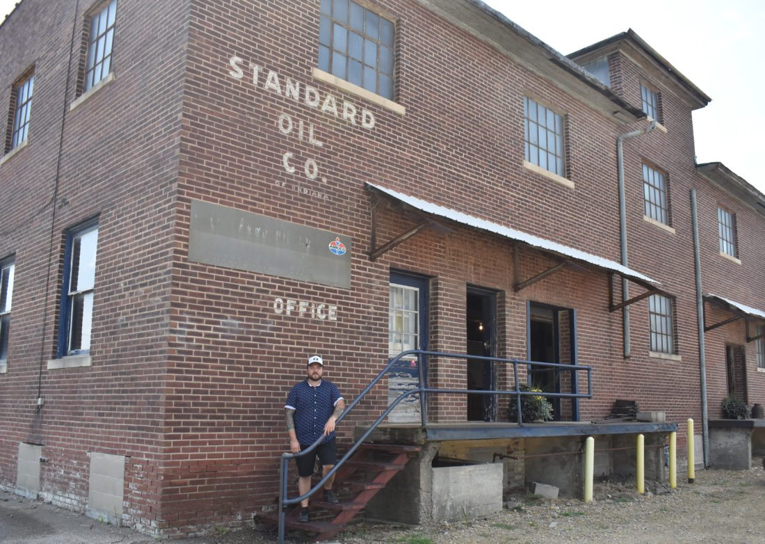 T-R PHOTO BY MIKE DONAHEY  Garrett Goodman of Marshalltown poses at the former Standard Oil building, 502 S. First St. He purchased the building in 2015, and plans to restore the historic structure into a entertainment venue serving beverages and food. The entrepreneur said previous experience working in Central Iowa restaurants and other businesses will be an asset.