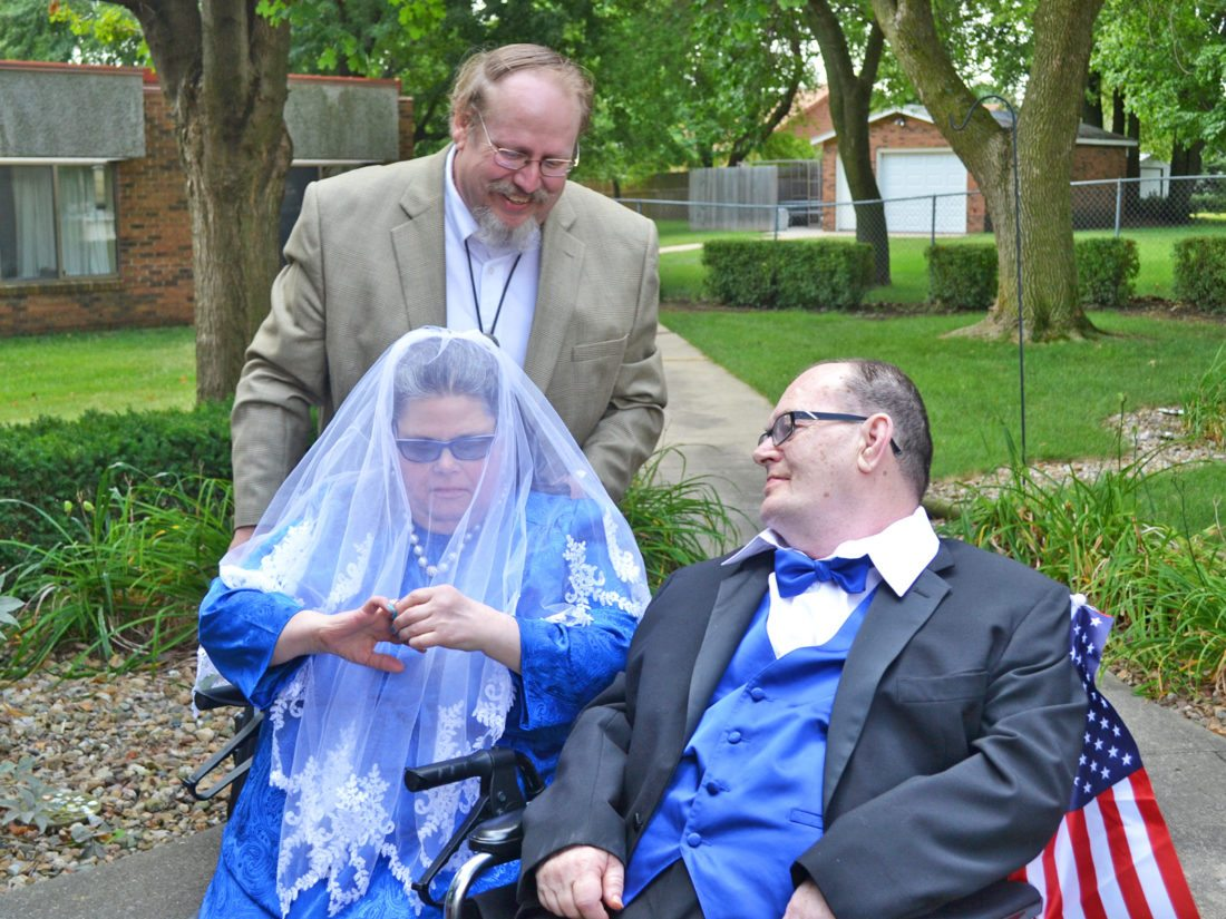 T-R PHOTO BY SARA JORDAN-HEINTZ AT LEFT:Mary Kline and George Miller professed their love for one another during a commitment ceremony held Monday afternoon at Hawkeye Care Center. David Shearer, minister of the Marshalltown Church of Christ, served as officiant. A reception followed, where a tiered blue and white wedding cake was served.
