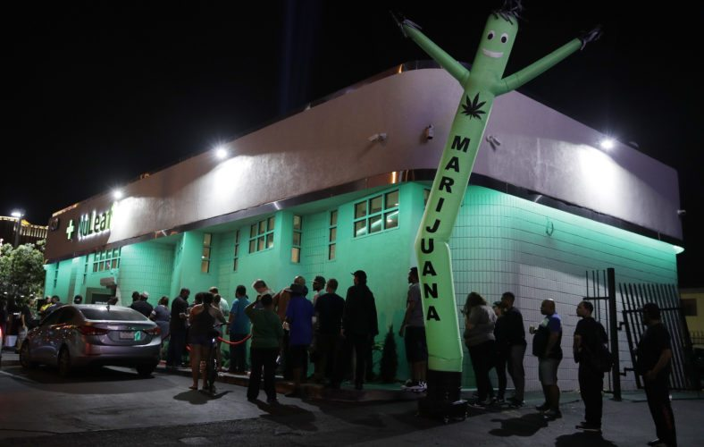 FILE- In this July 1, 2017, file photo, people line up at the NuLeaf marijuana dispensary in Las Vegas. A judge cleared the way Thursday, July 17, for Nevada to allow more businesses to move marijuana from growers to stores in an effort to keep up with overwhelming demand since recreational pot sales began last month. (AP Photo/John Locher, File)