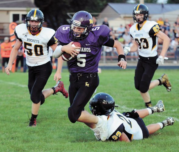 T-R PHOTO BY ROSS THEDE • East Marshall quarterback Tyler DeBondt (5) is tripped up from behind by Eddyville-Blakesburg-Fremont's Ryan Henkle (22) after an 11-yard scramble during the second quarter of the Mustangs' 22-18, season-opening win on Friday night in Le Grand.