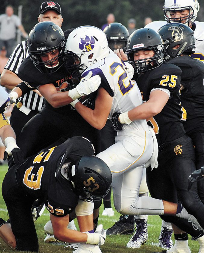 T-R PHOTO BY THORN COMPTON • A gang of Trojan defenders swarm Nevada running back Jakob Strottman during West Marshall's opening 14-13 double-overtime loss to the Cubs in State Center.