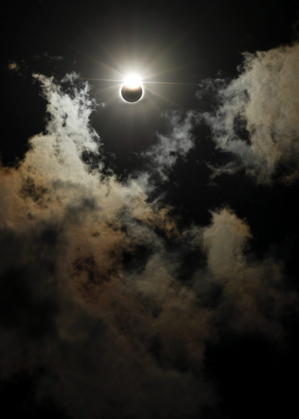 The moon partially blocks out the sun as a solar eclipse is seen through the clouds over the Gateway Arch Monday, Aug. 21, 2017, in St. Louis. The Gateway Arch was just a few miles outside of the path of totality. (AP Photo/Jeff Roberson)