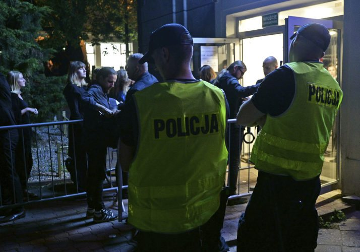 Police officers watch as spectators are checked by security guards as they enter a club for a concert by the American Allah-Las rock band, in Warsaw, Poland, Thursday, Aug. 24, 2017.  The band's concert in Rotterdam, The Netherlands was cancelled at the last minute by the police on Wednesday due to a terror threat. (AP Photo/Alik Keplicz)