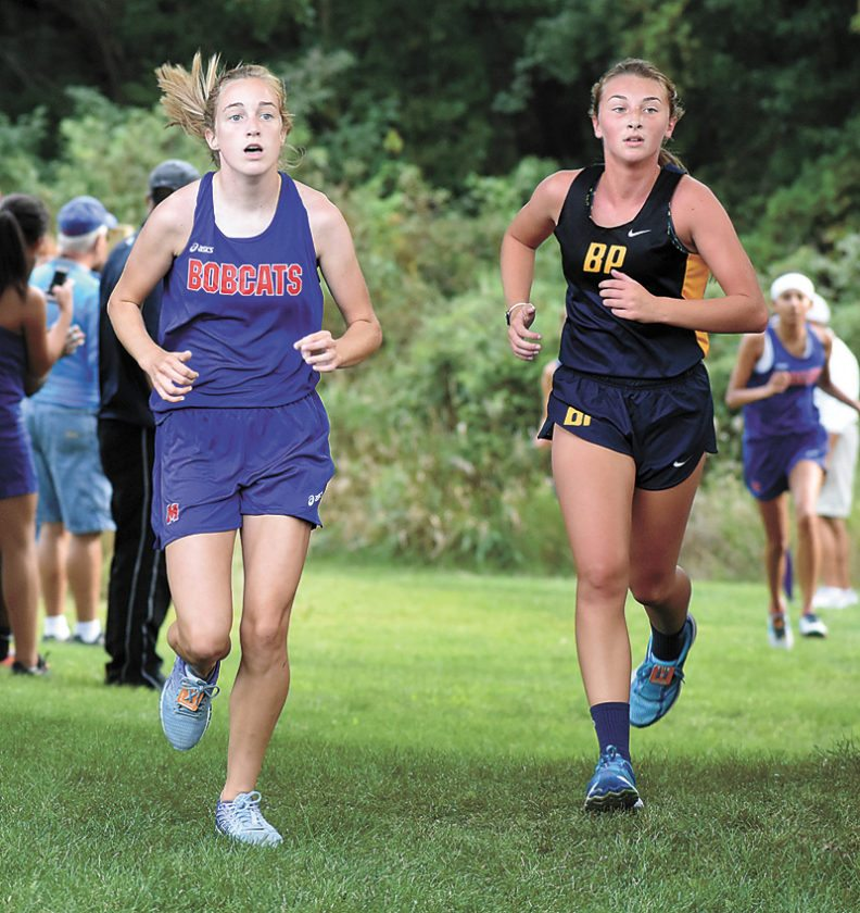 T-R PHOTO BY THORN COMPTON • Marshalltown freshman Mary Kate Gruening, left, runs alongside Belle Plaine's Lily Parrott during the Marshalltown Early Bird Meet on Thursday. Gruening was the highest finisher for the MHS girls, taking 24th in her first high school meet.