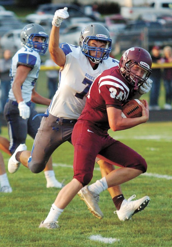T-R PHOTO BY ROSS THEDE • Grundy Center running back Caleb Kuiper (34) runs for 18 yards on third-and-14 before being brought down by Walker Thede of Gladbrook-Reinbeck during the first quarter of Friday's game in Grundy Center. Kuiper rushed for a game-high 121 yards in the Spartans' 28-7 loss.