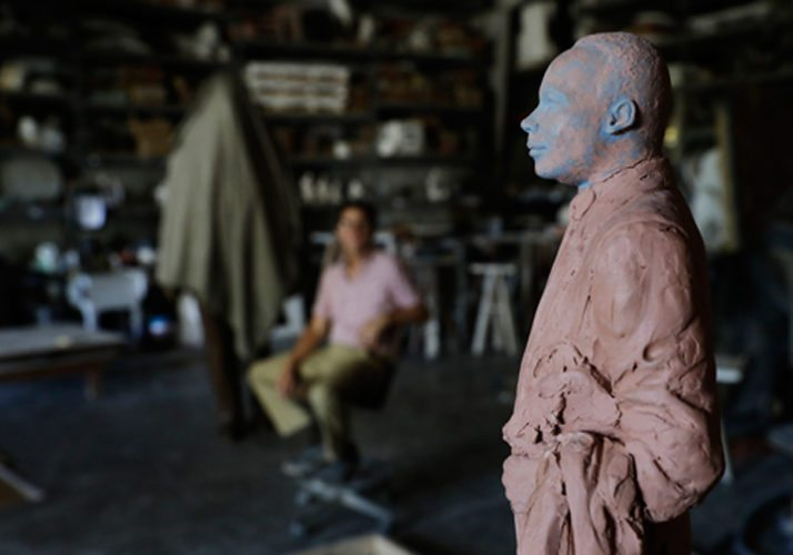 A model of a statue artist Martin Dawe, rear, sculpted paying tribute to civil rights leader Martin Luther King Jr., stands at right as the finished statue is covered at rear left, at Dawe's studio in Atlanta. More than three years after Georgia lawmakers endorsed the project, a statue paying tribute to King will be installed and unveiled on the state Capitol grounds Monday, Aug. 28. (AP Photo/David Goldman)