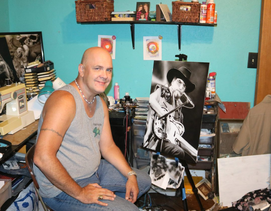 T-R PHOTO BY ADAM SODDERS A love of art and music helps U.S. Air Force veteran Dan Cahalan ease stress. He particularly enjoys making airbrush paintings of his favorite musicians, such as Waylon Jennings. Also in his art studio are several guitars, which he enjoys playing.