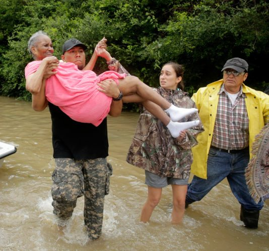 An elderly woman is carried to dry ground as she evacuates a neighborhood in west Houston inundated by floodwaters after water was released from nearby Addicks Reservoir when it reached capacity due to Tropical Storm Harvey on Tuesday, Aug. 29, 2017, in Houston, Texas. (AP Photo/Charlie Riedel)