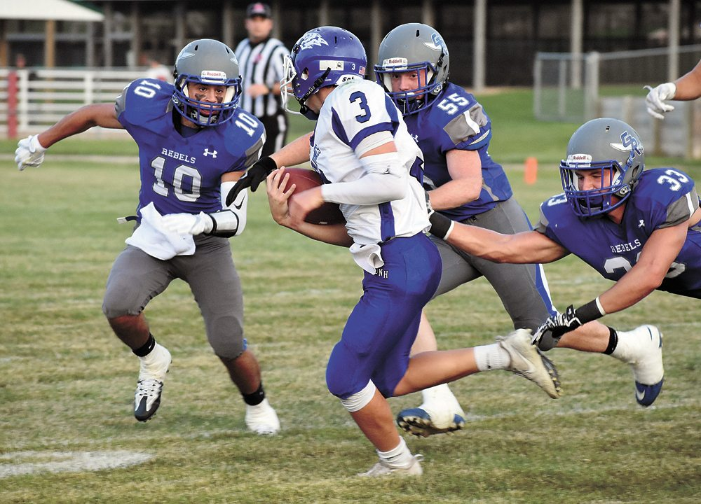 T-R PHOTO BY THORN COMPTON • Gladbrook-Reinbeck defenders Hunter Lott (10), Kyle Koppen (55) and Gage Murty (33) bear down on Dike-New Hartford quarterback Cade Fuller during the second half of the Rebels' 19-7 win over on Friday in Gladbrook.
