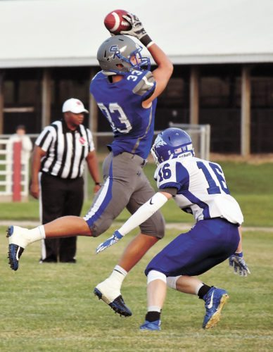 T-R PHOTO BY THORN COMPTON • Gladbrook-Reinbeck's Gage Murty (33) makes a leaping reception in front of Dike-New Hartford defender Grant Bixby (16) during the first half of Friday's non-district football game at The Pit in Gladbrook. Gladbrook-Reinbeck won its 25th-consecutive contest, beating the Wolverines 19-7.