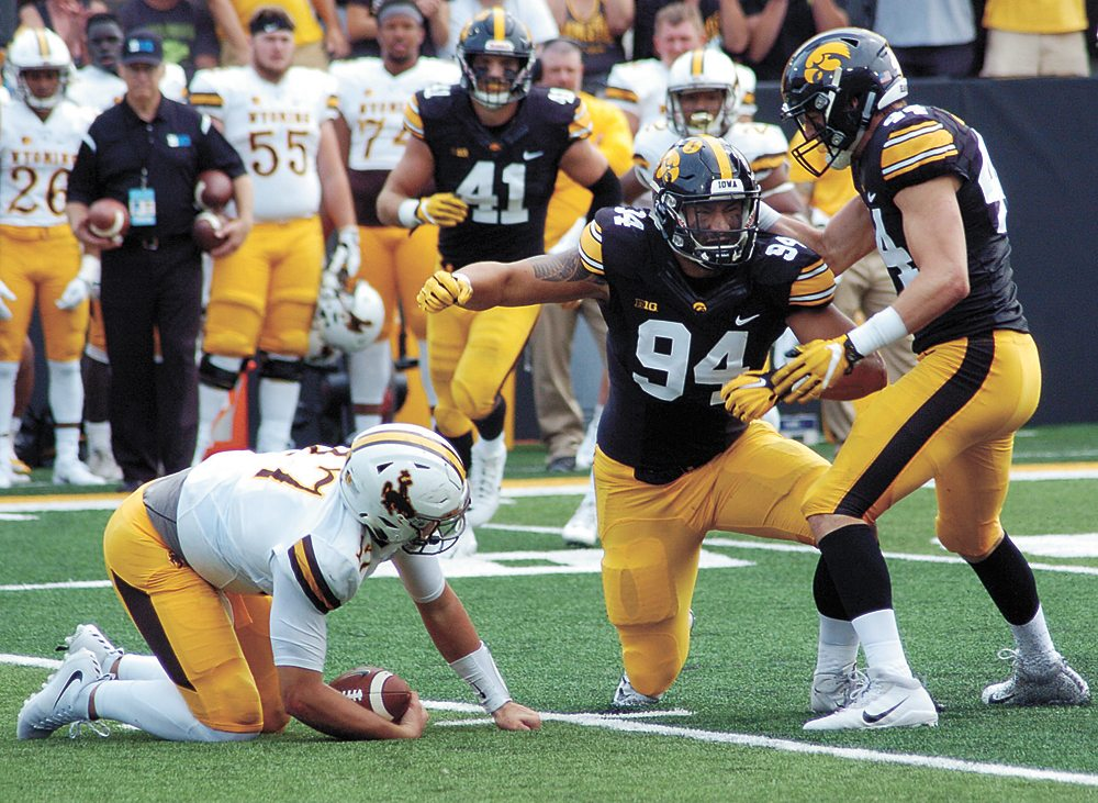 T-R PHOTO BY ROSS THEDE • Iowa freshman defensive end A.J. Epenesa (94) celebrates after sacking Wyoming quarterback Josh Allen, left, for a 3-yard loss during the second quarter of Saturday's game in Iowa City.