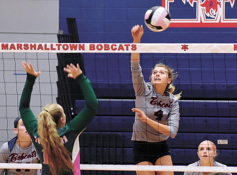 T-R PHOTO BY THORN COMPTON • Marshalltown senior Emily Hass (4) spikes the ball past Des Moines North's Megan Bohall during the Bobcats' three-set sweep of the Polar Bears on Tuesday at the Roundhouse. MHS not only swept the match, they won the final set by shutting out Des Moines North in rare 25-0 fashion.