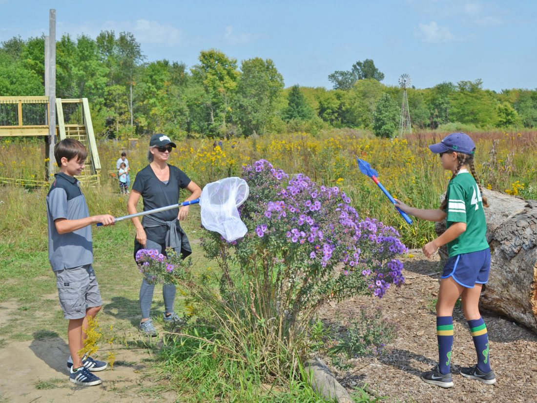 "T-R PHOTO BY SARA JORDAN-HEINTZ The second annual ""Monarchs and Milkweed for the Marshalltown Area"" program was held Saturday afternoon at the Marshalltown Public Library and at Grimes Farm. Attendees got the chance to catch and tag monarch butterflies, as this family did. Pictured is Yvette Meyer, and her children, Ethan and Natalie."