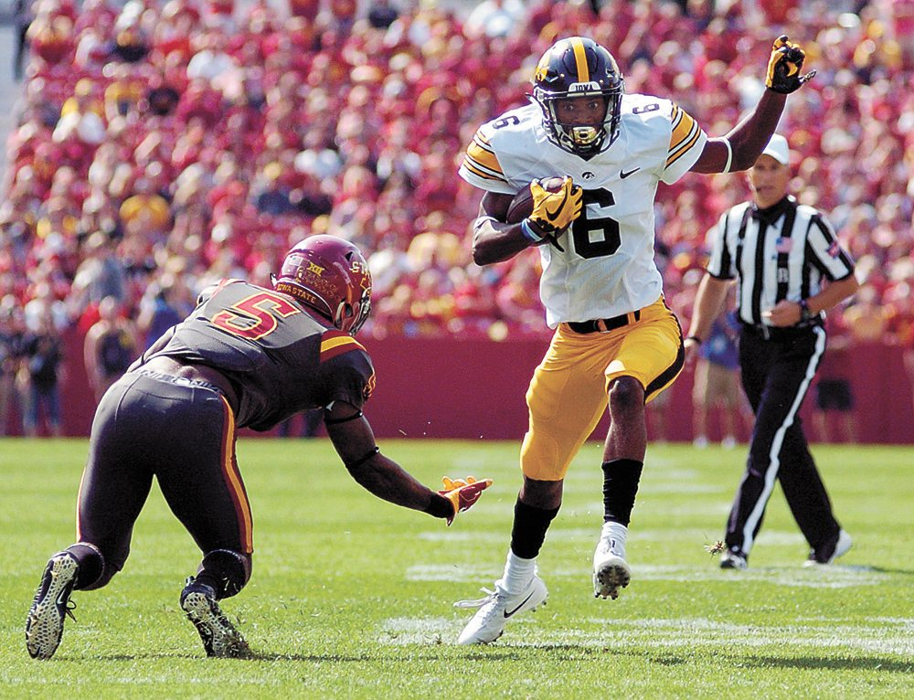 T-R PHOTO BY ROSS THEDE • Iowa freshman wide receiver Ihmir Smith-Marsette (6) sidesteps the tackle attempt by Iowa State safety Kamari Cotton-Moya in the first half of Saturday's game in Ames. Smith-Marsette caught two touchdown passes, including the 5-yard game-winner in overtime.