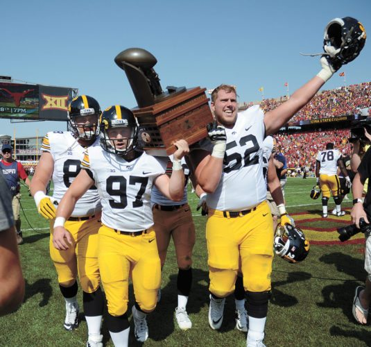 T-R PHOTO BY ROSS THEDE • University of Iowa long-snapper Tyler Kluver (97), a 2013 Marshalltown High School graduate, and offensive lineman Boone Myers (52) carry the Cy-Hawk Trophy across the field at Jack Trice Stadium in celebration of the Hawkeyes' 44-41, overtime victory over Iowa State on Saturday afternoon in Ames.