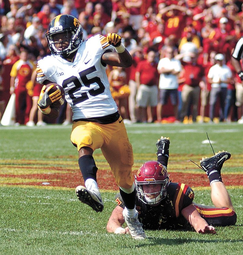 T-R PHOTO BY ROSS THEDE • Iowa running back Akrum Wadley (25) breaks free of Iowa State linebacker Joel Lanning on his way to a 46-yard touchdown reception during the fourth quarter of Saturday's college football game at Jack Trice Stadium in Ames.