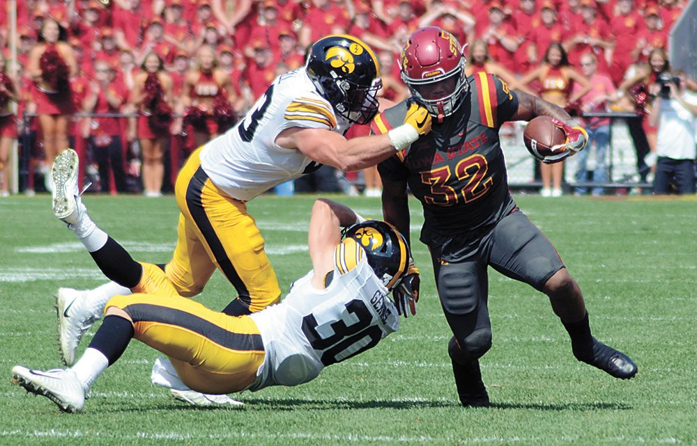 T-R PHOTO BY ROSS THEDE • Iowa State running back David Montgomery (32) tries to turn the corner against Iowa defenders Josey Jewell and Jake Gervase (30) during Saturday's game in Ames. Montgomery ran for 112 yards and a touchdown in the Cyclones' 44-41 overtime loss.