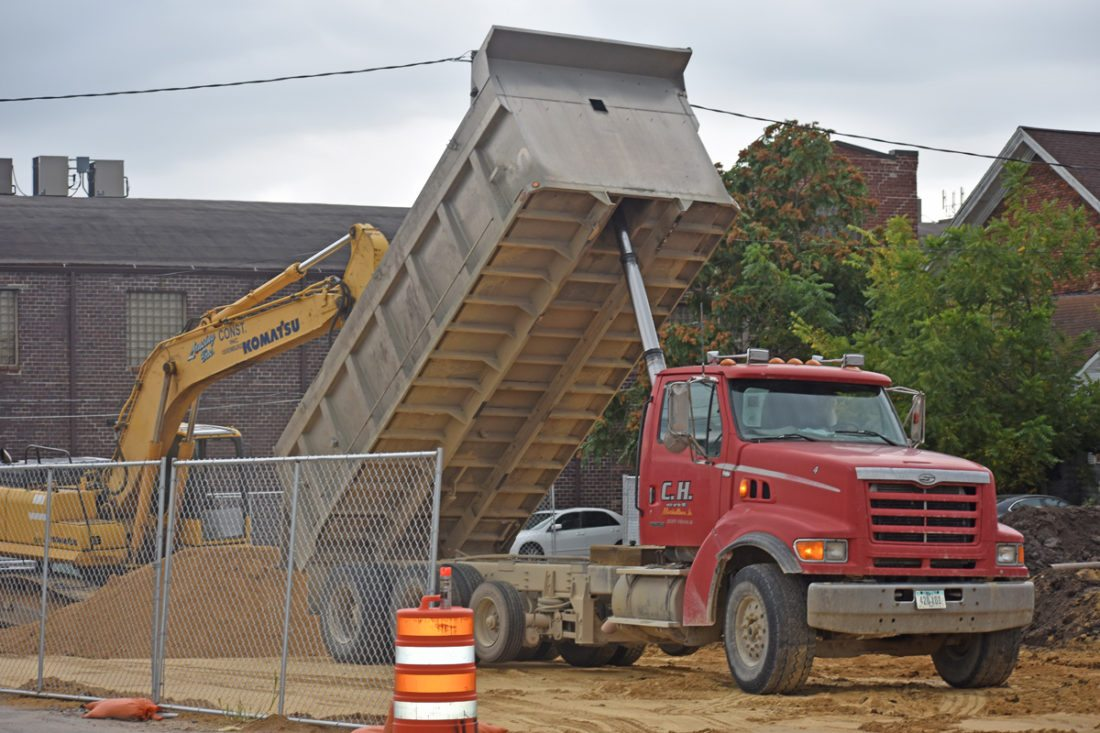 "T-R PHOTO BY MIKE DONAHEY  Dirt needed to fill and level-off ""The Vilager"" apartment complex site in the 100 block of North Center Street sits in a pile Monday, after being unloaded by a dump-truck,"