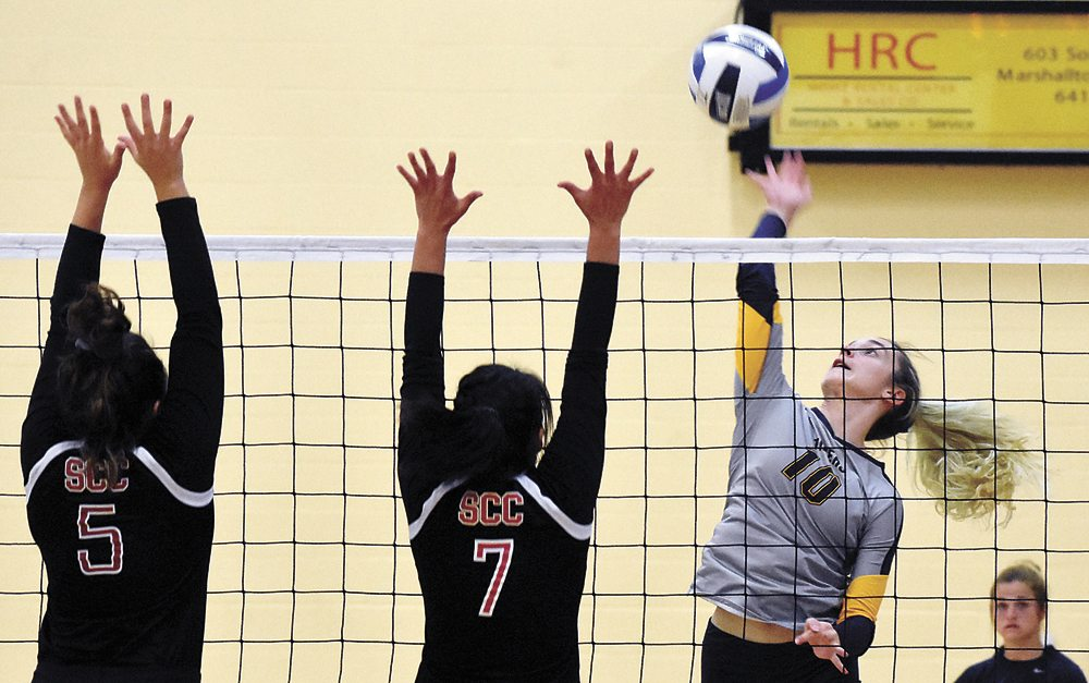 T-R PHOTO BY THORN COMPTON • Marshalltown Community College middle hitter Kaci Allgood (10) goes up for a kill against Kilie Akers (5) and Mariah Cook (7) from Southeastern Community College during the Tigers' home loss to the Blackhawks on Monday.